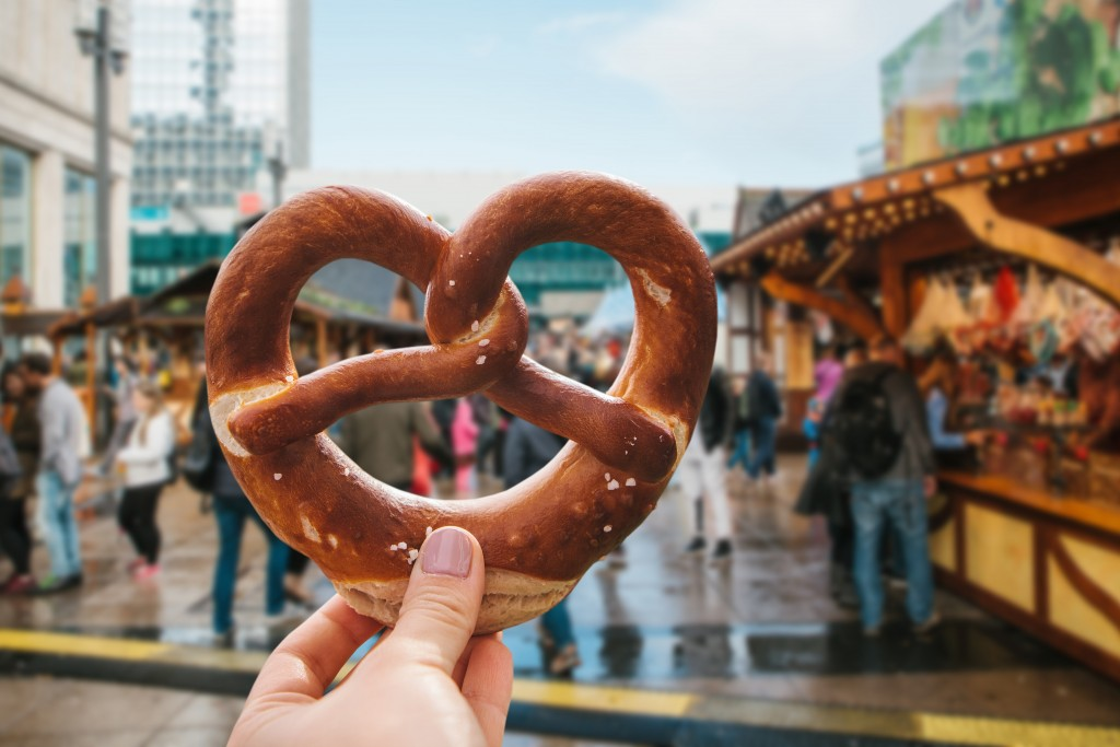 A girl or a young woman is holding a traditional German pretzel