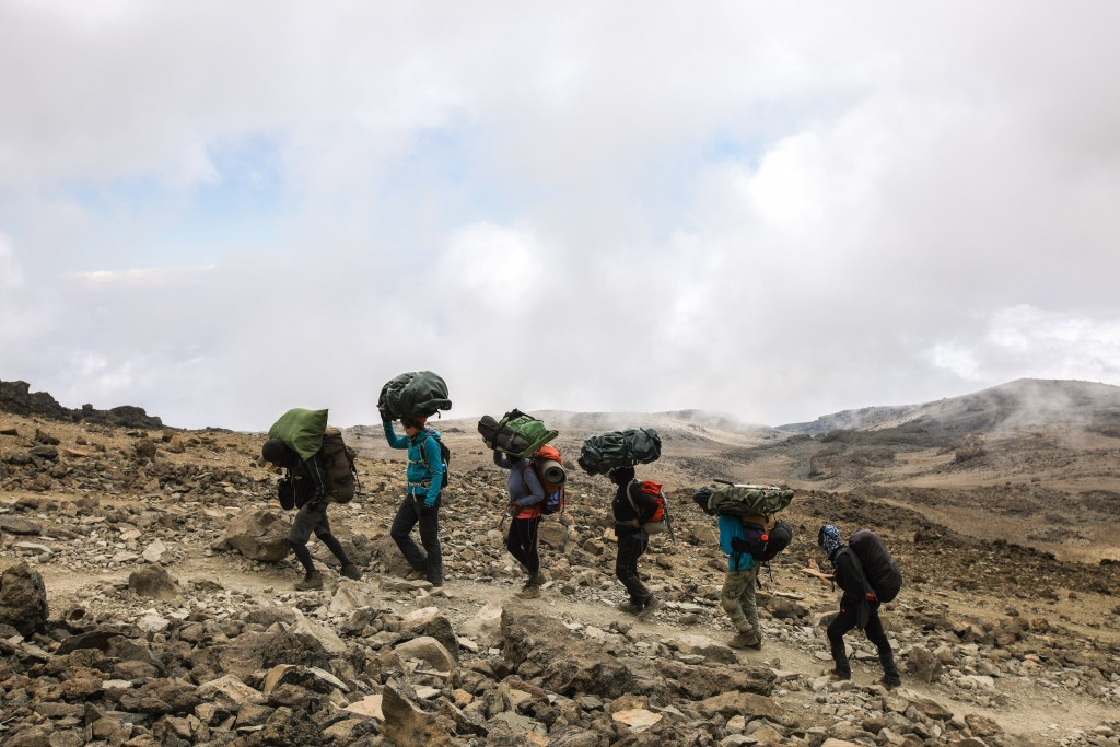 Image: Supplied by Exodus Travels. Crista Cullen (2nd from left) joined the porters in traditionally carrying her pack on her head.