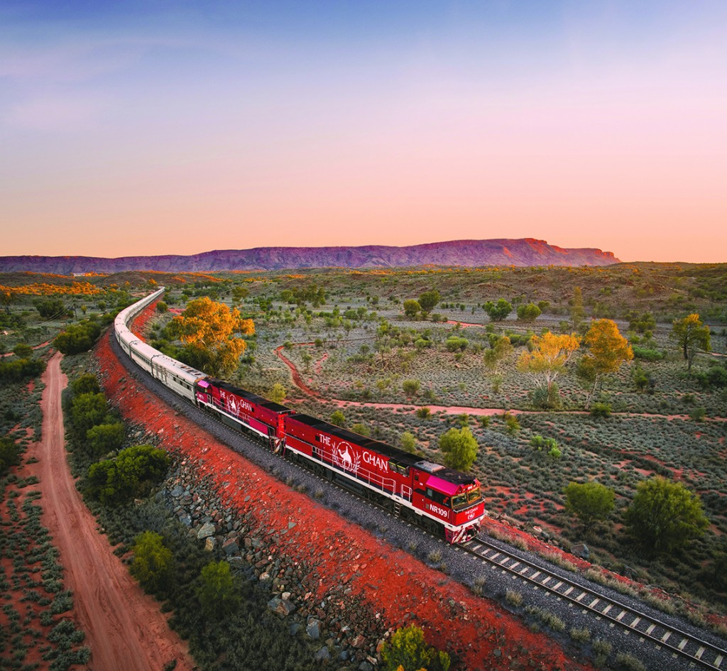 Rail Europe The Ghan heading north Alice Springs at sunset. MacDonnell Ranges in ...