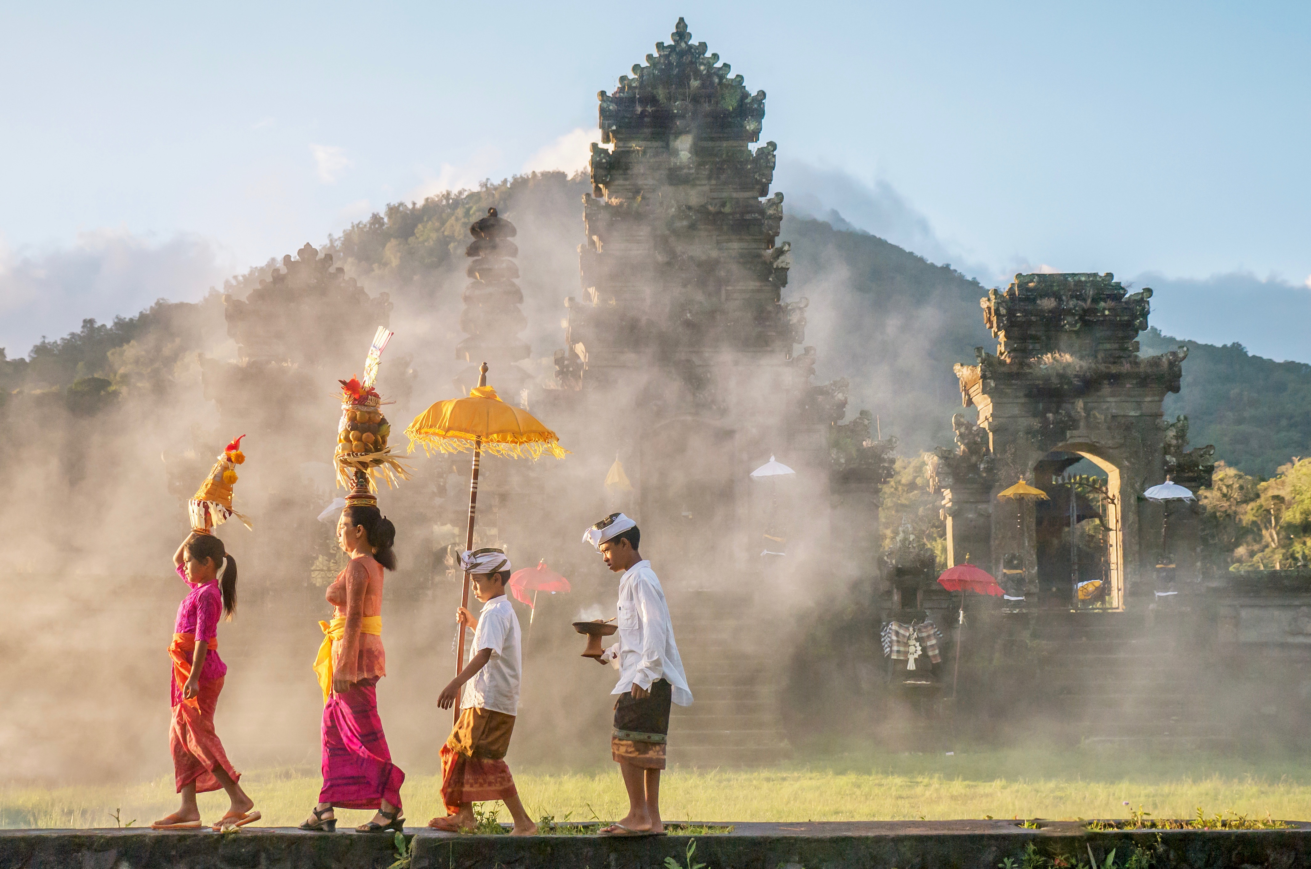 Showing traditional Balinese male and female ceremonial clothing and religious offerings as a mother and children walk to a Hindu temple (pura) in Bali.